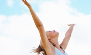 Smiling girl with arms raised towards the sky on sunny day